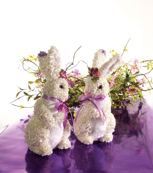 a greenery and pink flower arrangement and a couple of bunnies for an Easter centerpiece