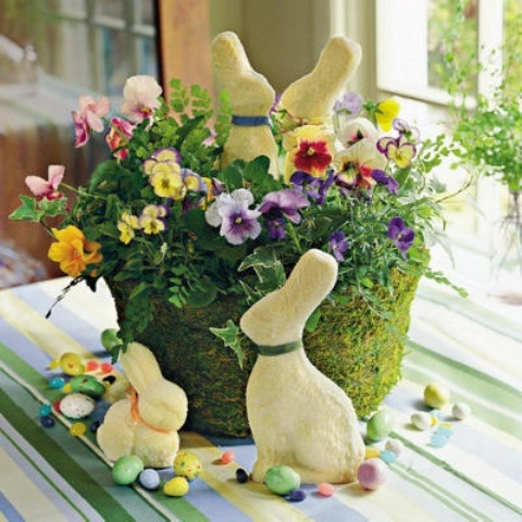 a moss basket with colorful pansies, colorful faux eggs and bunnies