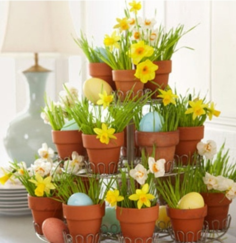 a cake stand with pots filled with grass, yellow daffodils and pastel eggs for an Easter party