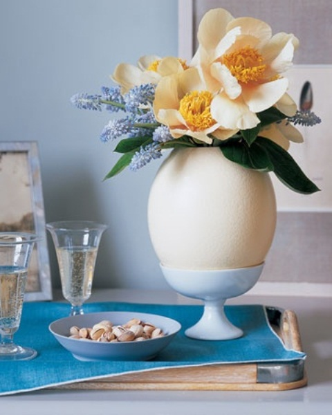 a spring flower arrangement placed into an oversized fake egg on a stand for Easter decor