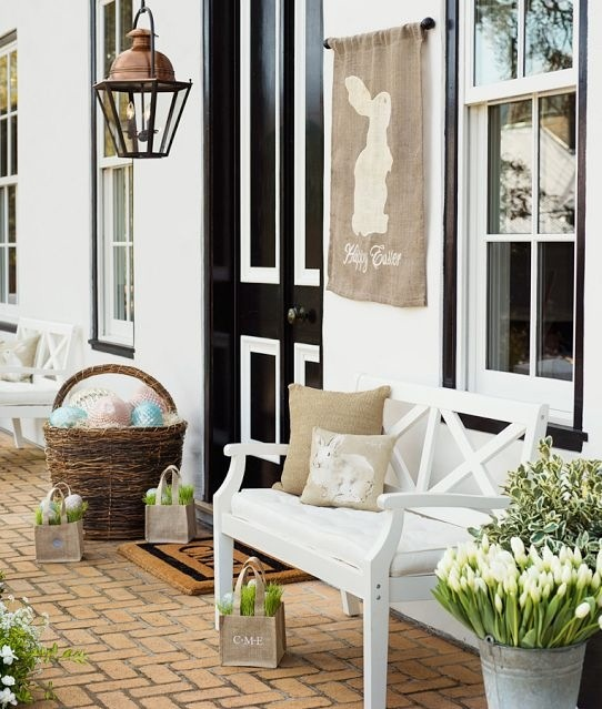a cozy farmhouse Easter porch with fresh spring blooms in buckets and bags, with oversized colorful eggs in a basket and a bunny banner