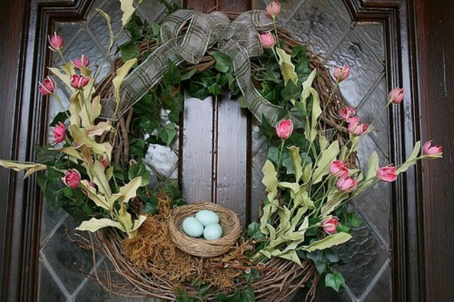 a bright spring wreath with a ribbon bow and a faux nest with eggs