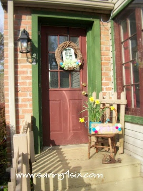 bright Easter porch styling with a colorful egg wreath, spring daffodils in a watering can and a colorful crate