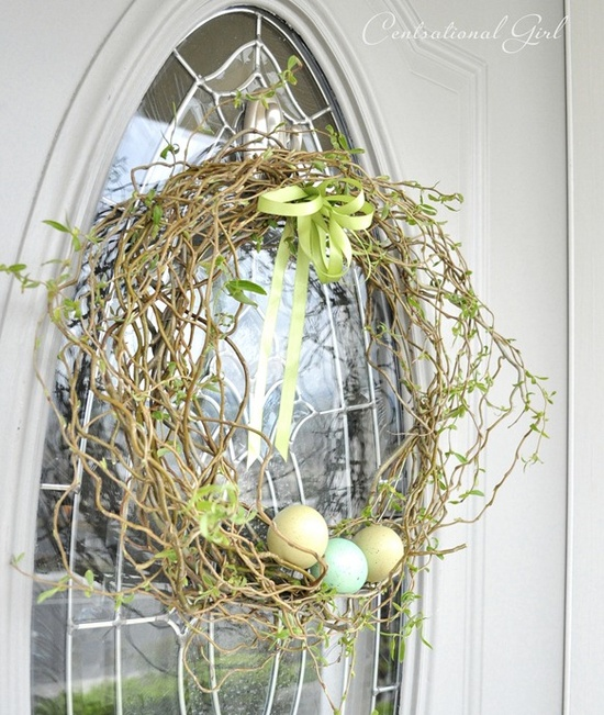 a fresh and green Easter wreath with colorful eggs in it and a bow on top