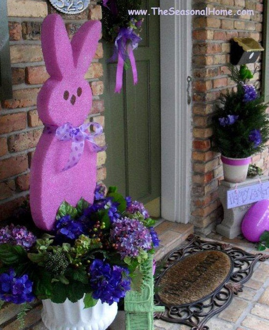 a colorful Easter bunny and oversized egg plus purple blooms in the pots
