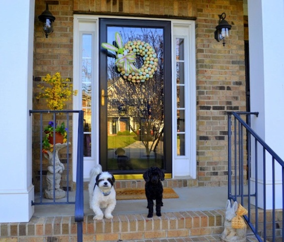 simple porch styling with a colorful egg wreath, yellow potted blooms and a vintage stone bunny