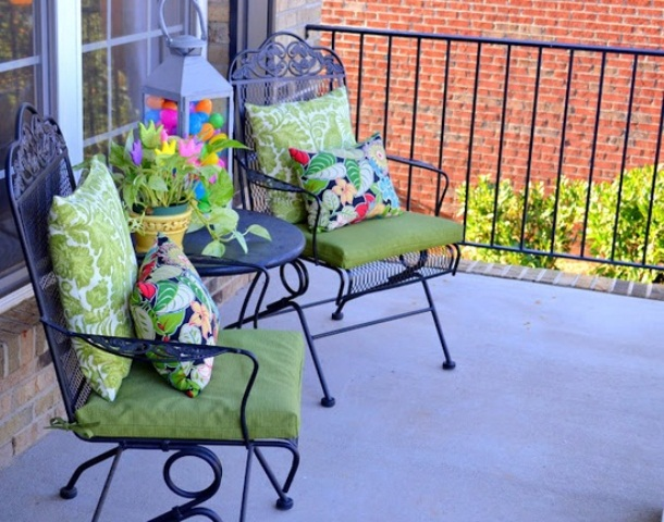 a duo of chairs with colorful pillows, a lantern with colorful eggs and bright blooms in a pot