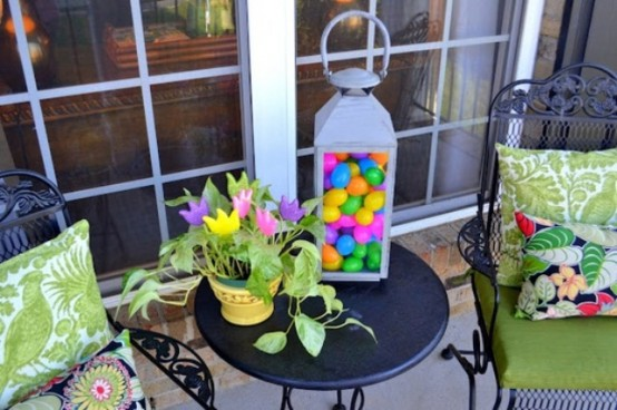 a large lantern filled with colorful eggs, colorful paper blooms in a basket for Easter