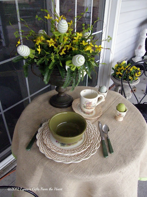 a table styled on the front porch with a greenery and floral arrangement with eggs, some colorful eggs and porcelain