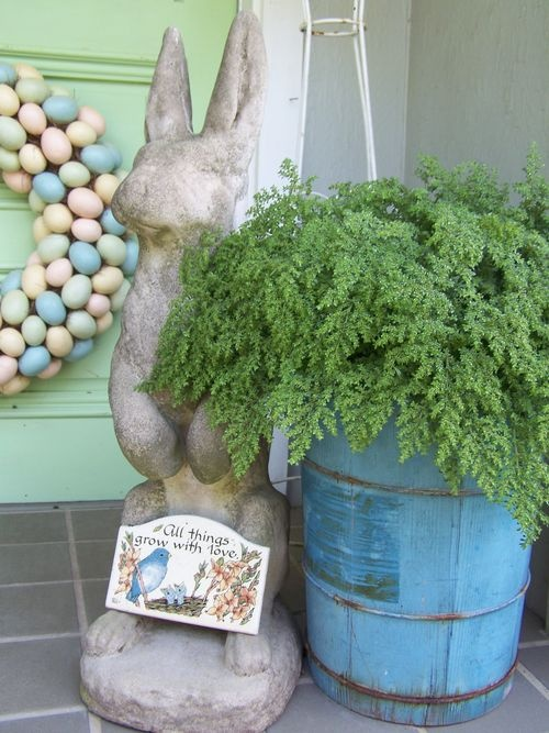 a blue wooden bucket with greenery, a colorful egg wreath and a vintage bunny for decor