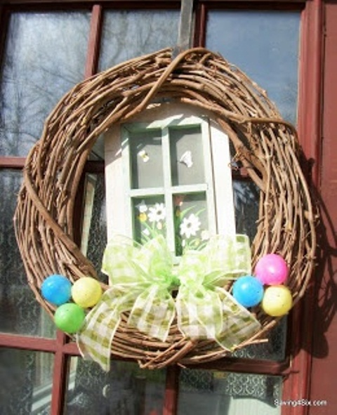 a spring wreath with colorful eggs, a bright bow and a vintage window piece with decor