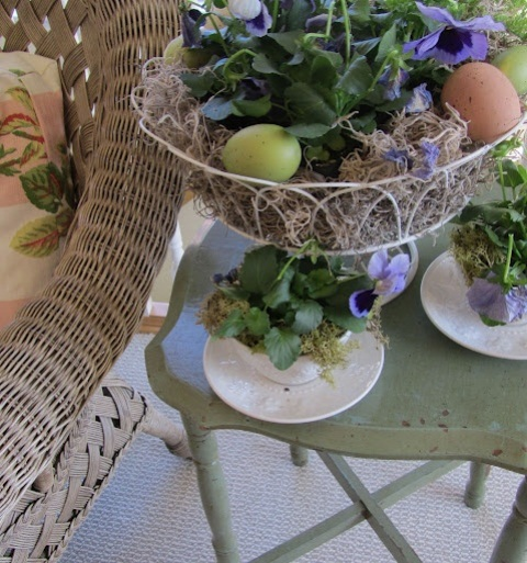 a wire basket with colorful blooms and eggs and some blooms planted into a vintage teacup