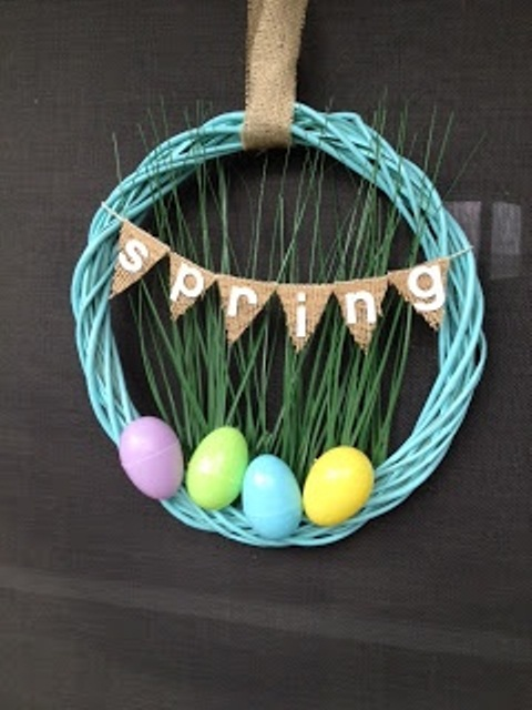 a colorful wire wreath with fake grass, colorful eggs and a bunting