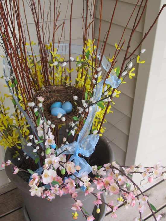 a spring arrangement with spring blooms and blooming branches and a fake nest plus eggs