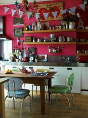 an eclectic kitchen with hot pink walls, stainless steel appliances and a backsplash, a wooden table and pastel chairs