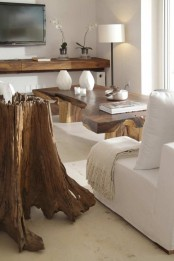 a piece of driftwood as a statement art piece in a modern space, and some staiend wood furniture that echoes with it