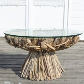a unique dining table, the base of which is fully composed of driftwood and with a round glass tabletop is a fantastic solution and an eco-friendly decoration