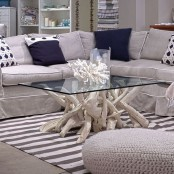 a lovely driftwood coffee table of whitewashed driftwood with a glass tabletop is a stylish idea for any sea-inspired interior