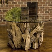 a large table made of driftwood and a round glass tabletop can be used as a lovely console or coffee table, both indoors and outdoors