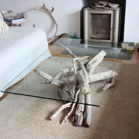 a refined modern coffee table made of driftwood for the base and a sheer glass top to enjoy this wood through it