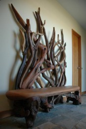 an entryway decorated with dark stained driftwood and a matching bench with legs made of driftwood, too, is a unique idea for a bold natural statement