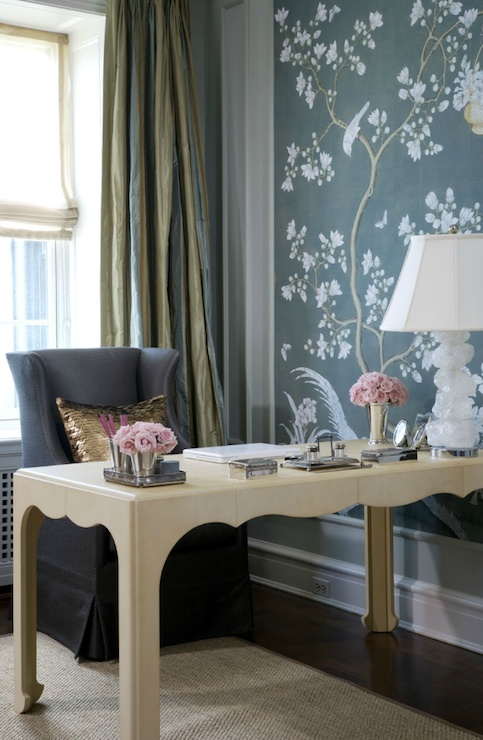 a romantic feminine home office with a blue floral accent wall, a beautiful carved desk and a a grey chair plus a refined table lamp
