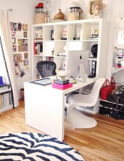 a vivacious feminine home office with an open storage unit, a desk, some chairs and a zebra rug plus bright pink touches