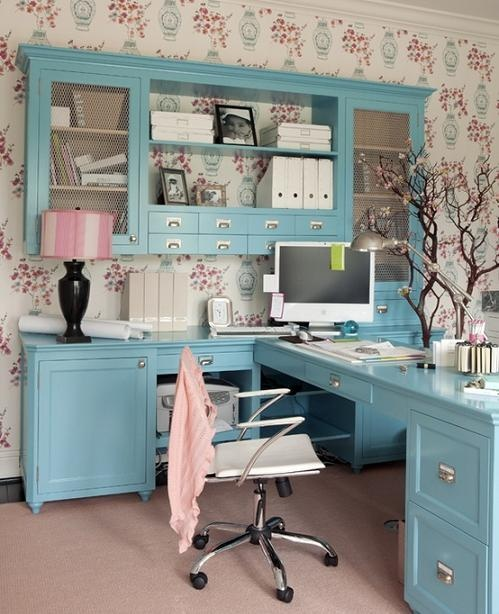 a cute feminine home office with floral wallpaper, blue furniture, table lamps and blooming branch decor