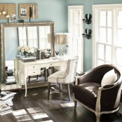 a refined powder blue home office with a statement mirror, a white desk, a brown sofa and touches of elegant decor