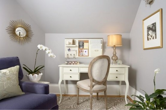 a small yet elegant home office with grey walls, a purple sofa, a refined white desk and a chair plus potted orchids