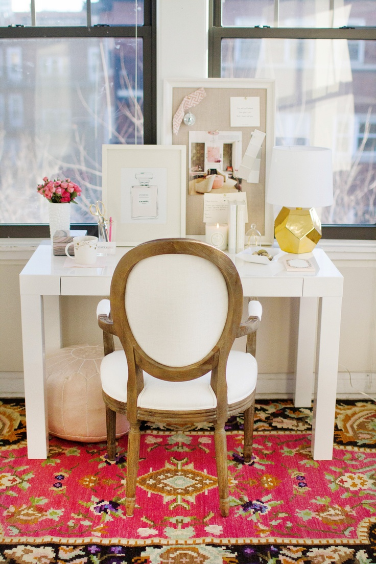 a bright feminine home office with neutral walls, a white desk and a chair, a bright printed rug and touches of gold