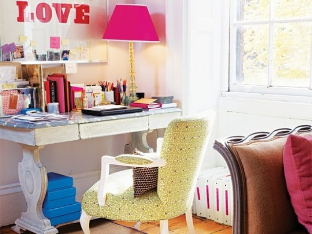 a vibrant feminine home office with an exquisite desk, a green chair, a pink lamp and decorations