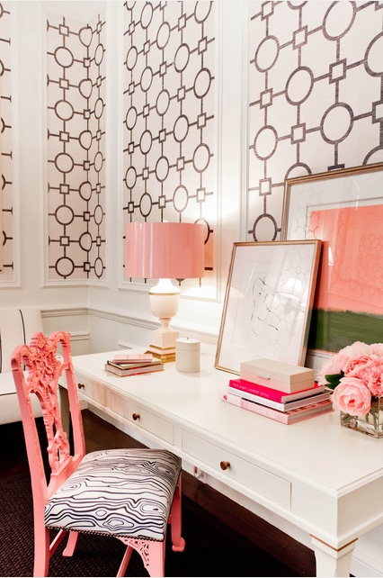 an elegant home office with printed black and white wallpaper, a white desk, a pink lamp and artworks and a pink printed chair