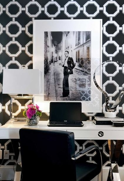 an elegant black and white home office with printed wallpaper, a white desk, black chair, chic artworks and a white table lamp