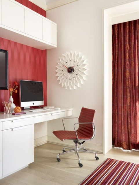 a bright red and white home office with printed red wallpaper, a curtain and a rug plus a red leather chair