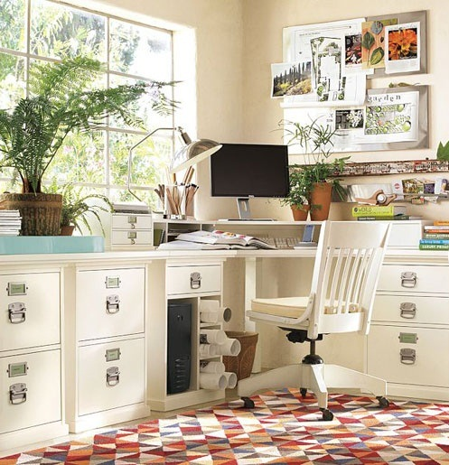 a comfortable home office done in neutrals, with cool storage furniture, a bright rug and some potted greenery