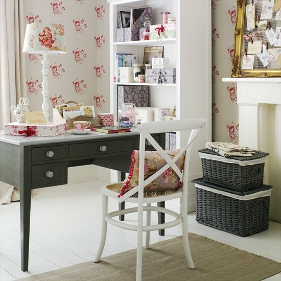 a chic vintage feminine home office with floral wallpaper, a dark desk, dark woven boxes and a non-working fireplace