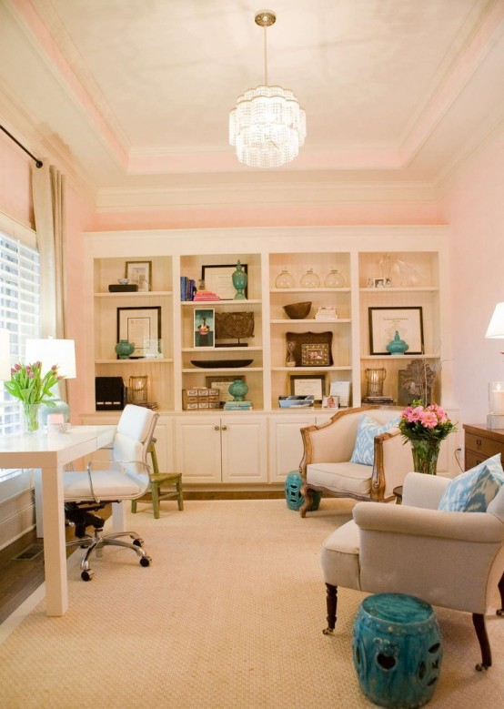 an elegant blush home office with a large storage unit that takes a whole wall, more neutral furniture and a crystal chandelier plus touches of blue