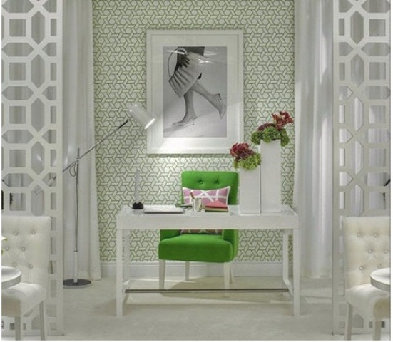 a stylish green and white girlish home office with printed wallpaper,  white furniture, a green art and cool art