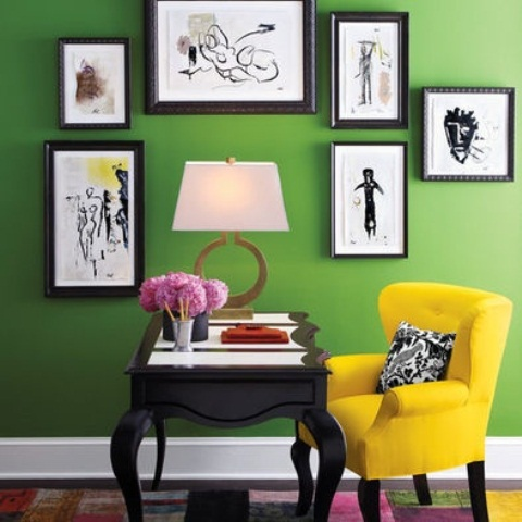 a colorful home office - green walls plus a yellow chair balanced with a black carved desk and a black and white gallery wall