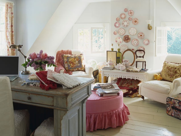 an attic shabby chic and vintage home office with a shabby desk, refined chairs, a pink decorative plate arrangement and a pink ottoman