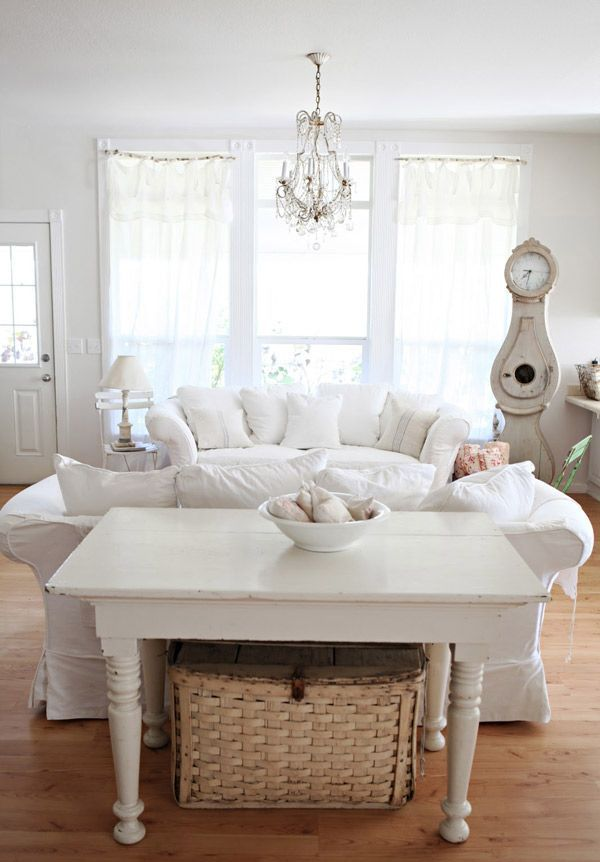 a white shabby chic living room with chic furniture, neutral textiles, a crystal chandelier and vintage accessories and decor