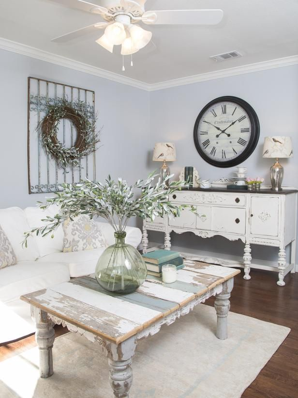 a shabby chic living room with pastel blue walls, refined neutral furniture, a wreath and a clock, a low table and neutral linens
