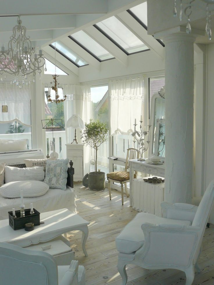 a white shabby chic living room with skylights, elegant white furniture, a crystal chandelier, a potted plant and greenery