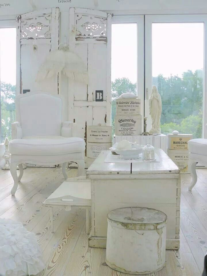 a white shabby chic living room with elegant furniture, a carved wooden screen, angel wings and antique accessories