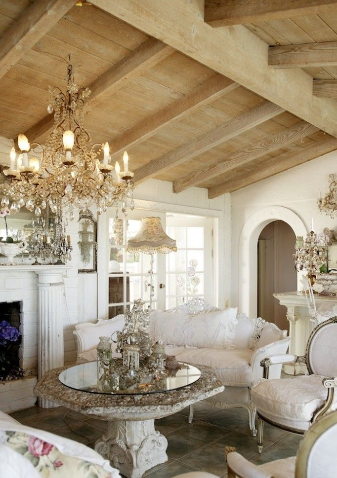 a refined French shabby chic living room with wooden beams, a fireplace, elegant and chic furniture, a crystal chandelier and a gorgeous stone table