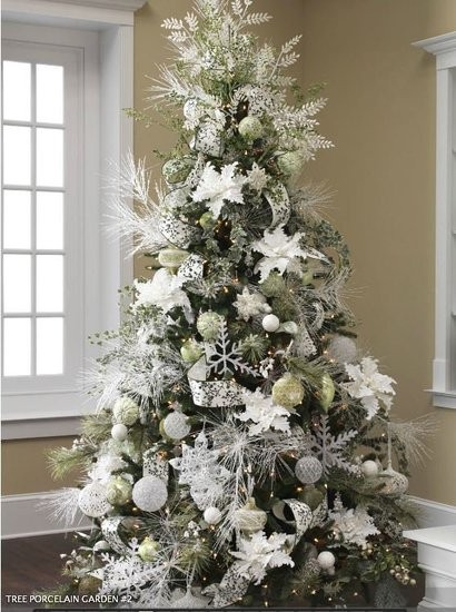 a Christmas tree with white and silver ornaments - balls, snowflakes, stars, snowy greenery and shiny ribbons