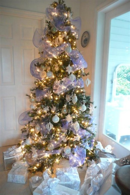 a Christmas tree with lights, silver and white Christmas ornaments, ribbons and snowflakes looks frozen-like