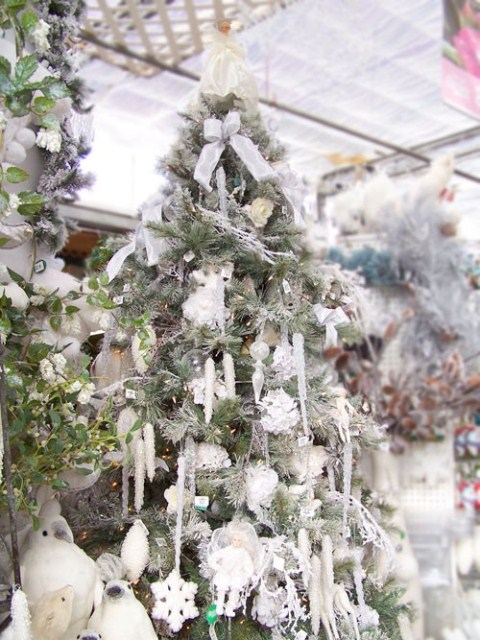 a snowy Christmas tree with snowflake and other ornaments, icicles and bow ornaments in silver and white