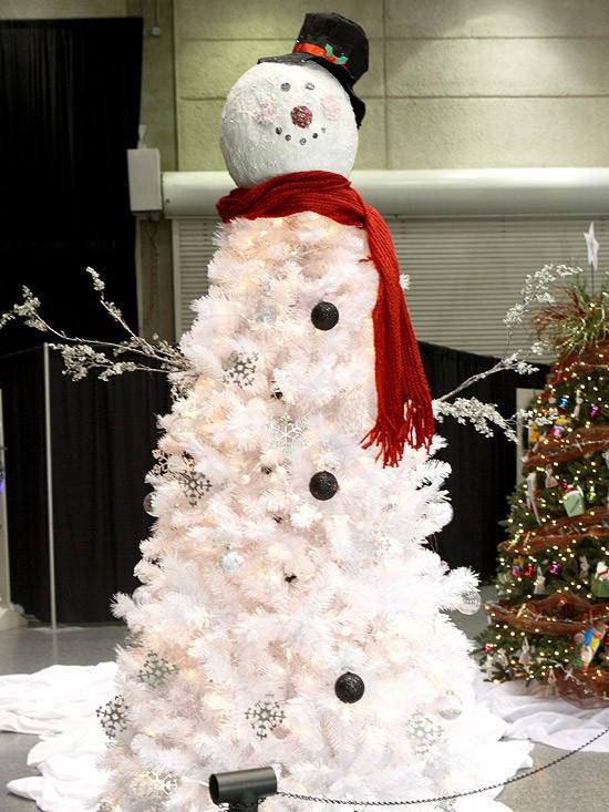 a white snowman Christmas tree with lights and some black ornaments plus a snowman head and arms